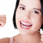 Beautiful young woman using dental floss